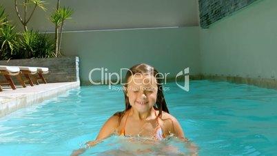 Young girl having fun in the swimming pool