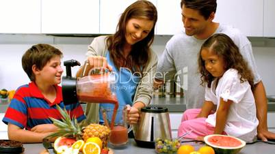 Woman with family pouring fruit cocktail from a blender
