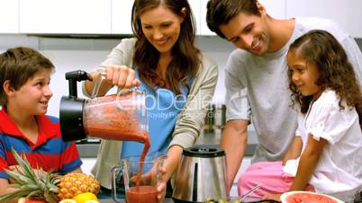 Smiling woman with family pouring fruit cocktail from a blender