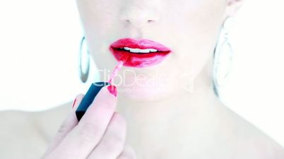 Attractive woman putting lipstick on her lips