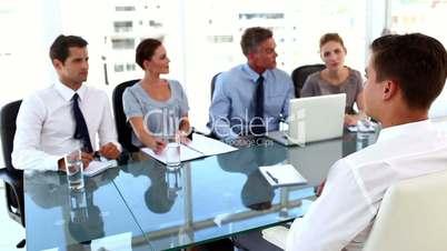 Business team giving a job interview to a businessman