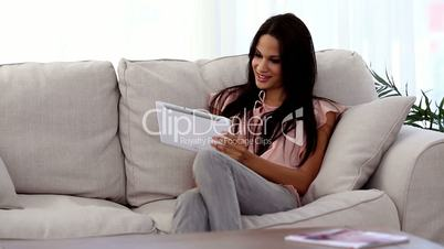 Attractive woman using tablet pc on the couch