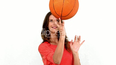 Woman having fun with a basket ball on white background