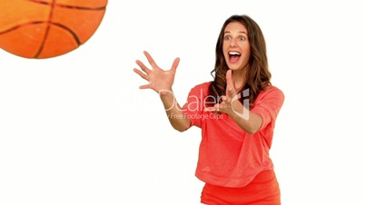 Cheerful woman catching a basketball on white background