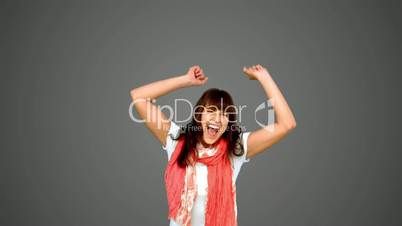 Brunette woman jumping on grey background