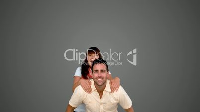 Smiling man giving to his friend a piggyback on grey background