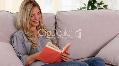Blonde woman reading book at home and smiling