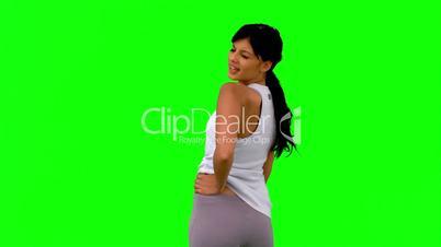 Woman in sportswear turning against green screen