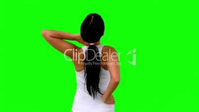 Woman in sportswear stretching her back on green screen