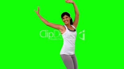 Woman in sportswear jumping on green screen