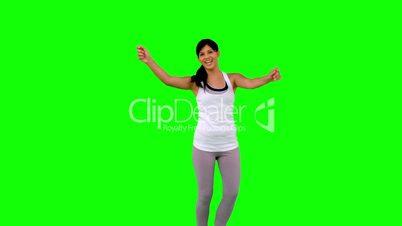 Woman in sportswear dancing on green screen