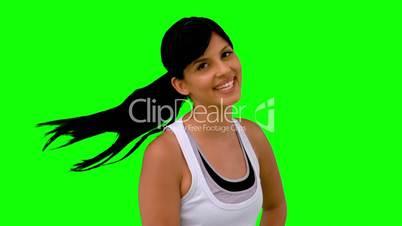 Woman in sportswear tossing her hair on green screen