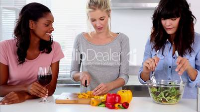 Attractive friends preparing salad in the kitchen