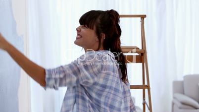 Attractive woman jumping to paint her wall