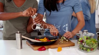 Three friends preparing a meal together