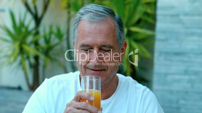 Retired man drinking orange juice outside