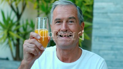 Retired man toasting with orange juice outside