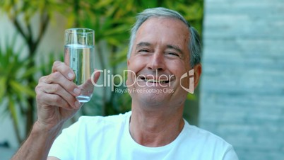 Retired man toasting with water outside