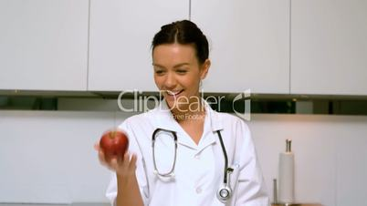 Home nurse throwing and catching apple and smiling in kitchen