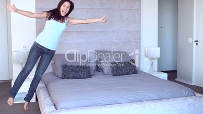 Pretty woman leaping onto bed