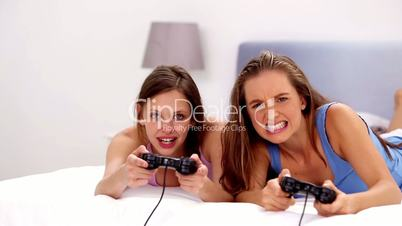 Girls playing video games on bed