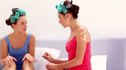 Girls in hair rollers painting each others nails