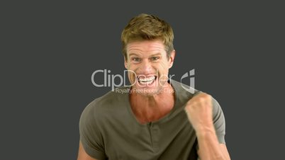 Man showing his happiness on grey screen