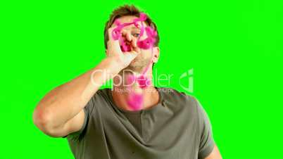 Man blowing pink confetti on green screen