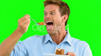Man savouring a delicious cake on green screen