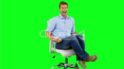 Smiling man turning on swivel chair on green screen