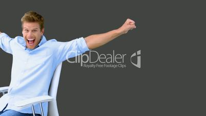 Man on swivel chair raising arms to show his success on grey screen