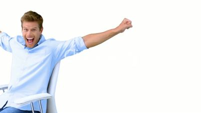 Man on swivel chair raising arms to show his success on white screen