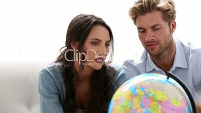 Couple looking at globe and picking travel destination