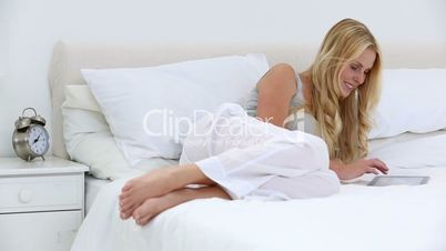Blonde woman using tablet in bed