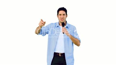 Man singing into microphone and dancing on white background