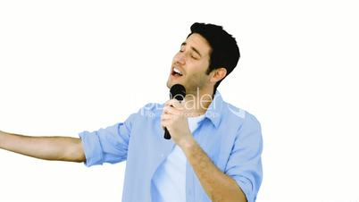 Man singing into microphone with emotion on white background