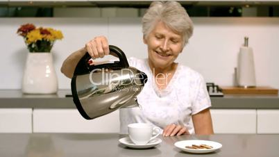 Elderly woman pouring boiling water from kettle into cup in kitchen