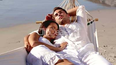 Attractive couple sleeping together in a hammock