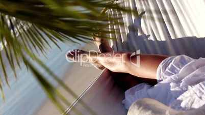 Woman relaxing in a hammock under a palm tree