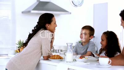 Mother chatting to children at family breakfast
