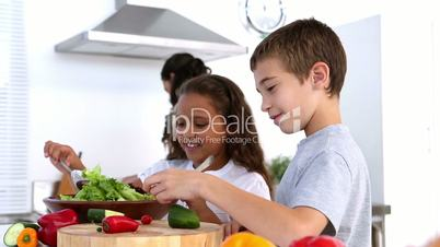 Siblings making salad together with mother watching