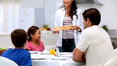 Mother bringing pizza to dinner table