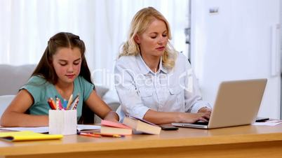 Mother working on laptop with daughter doing homework
