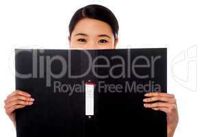 Chinese woman hiding face with business file