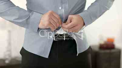 Frustrated angry man trying to button up a tight shirt