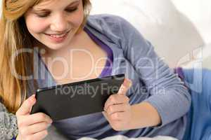 Friendly teenage girl reading on digital tablet