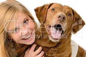 Adolescent girl embracing her golden retriever