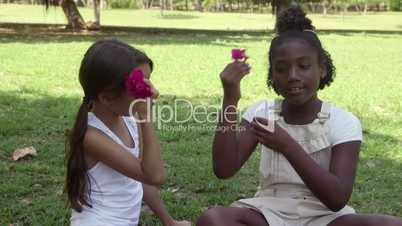 Friends and fun, girls talking, laughing while playing with flower