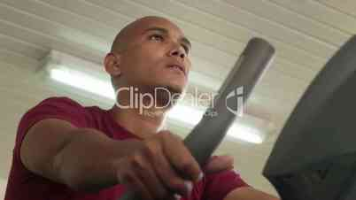 People exercising in gym, adult hispanic man training on bicycle