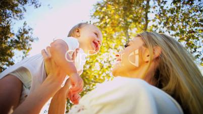 Blonde Mom and Baby Laughing Outdoors
